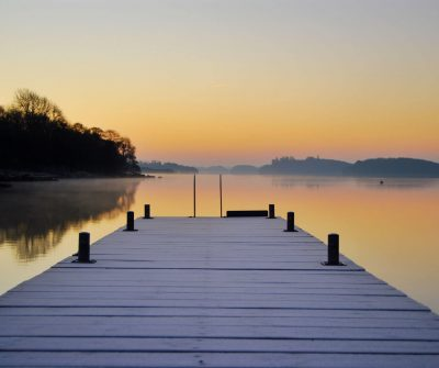 View from a jetty over Lough Erne on a calm frosty morning with a glowing orange sky