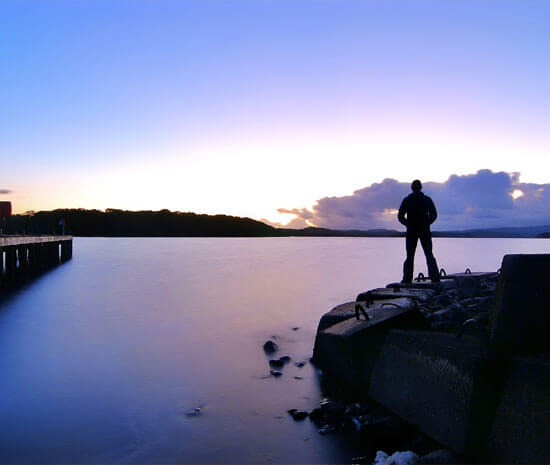 Man standing alone looking out over a lake towards a sunset